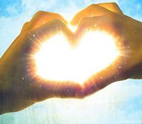 Hands forming heart shape and burst of light