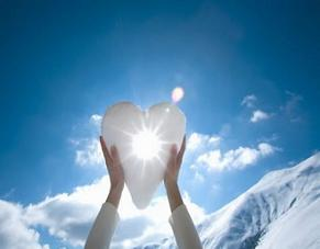 Hands holding snow shaped heart with burst of sunlight